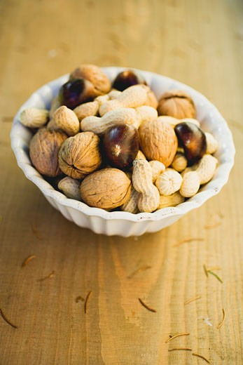 Walnuts, chestnuts and peanuts in white bowl : Stock Photo
