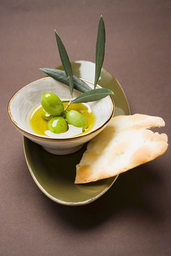 Green olives on twig in bowl of olive oil, crackers : Stock Photo