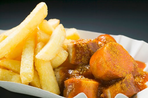 Currywurst (sausage with ketchup & curry powder) & chips in paper dish : Stock Photo
