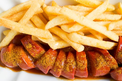 Currywurst (sausage with ketchup & curry powder) & chips (detail) : Stock Photo