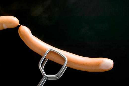 Stock Photo: 1532R-29204 Tongs holding frankfurters