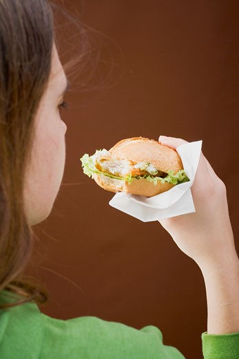 Girl eating a breaded escalope in a bread roll : Stock Photo