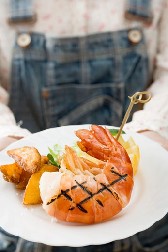 Stock Photo: 1532R-29683 Person holding grilled king prawn on plate