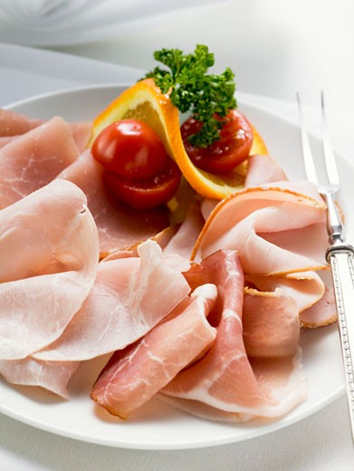 Stock Photo: 1532R-29795 Platter of ham with cherry tomatoes, orange and parsley