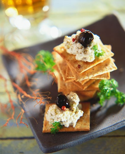 Aubergine cream and black olives on crackers : Stock Photo