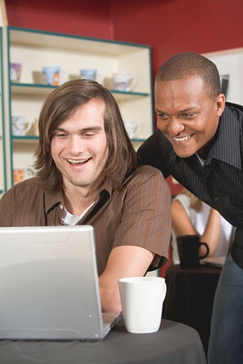 Two men in café looking at a laptop with interest : Stock Photo
