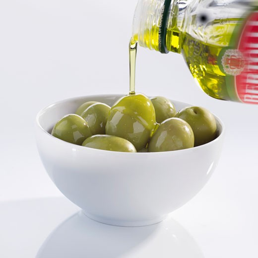 Pouring olive oil over olives : Stock Photo