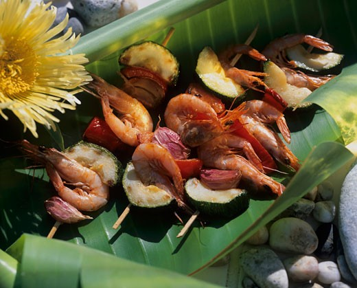 Skewered prawns, courgettes and garlic on banana leaf : Stock Photo
