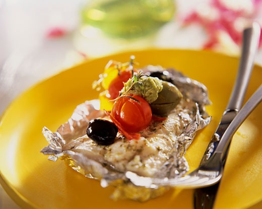 Fish fillet with pesto, tomatoes & olives on aluminium foil : Stock Photo