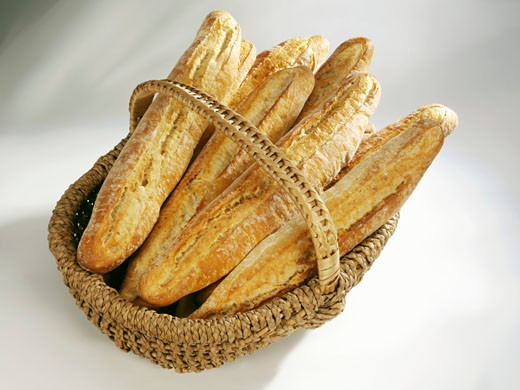 Crusty French loaves in a basket : Stock Photo