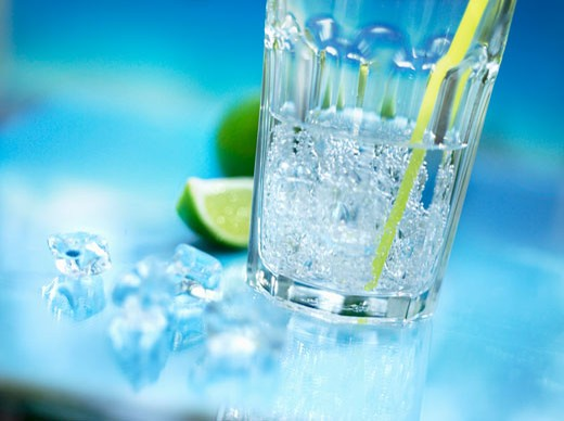 Stock Photo: 1532R-31468 A glass of mineral water with straw, crushed ice and lime