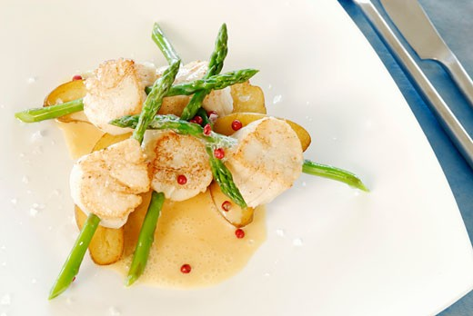 Scallops speared on asparagus with butter sauce : Stock Photo