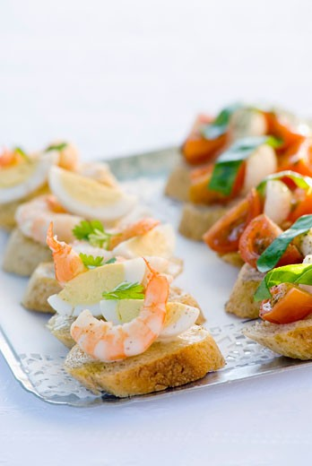 Canapés with prawn, egg, tomato, mozzarella on tray : Stock Photo