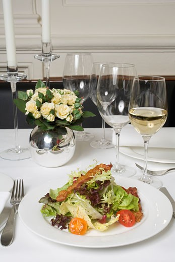 Salad with bacon & glasses of white wine on laid table : Stock Photo