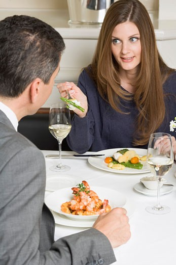 Stock Photo: 1532R-32604 Woman offering man asparagus on fork in restaurant