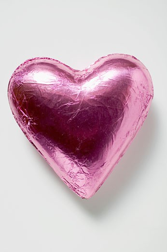 Chocolate heart in pink foil : Stock Photo
