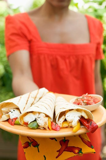 Woman holding plate of wraps and salsa : Stock Photo