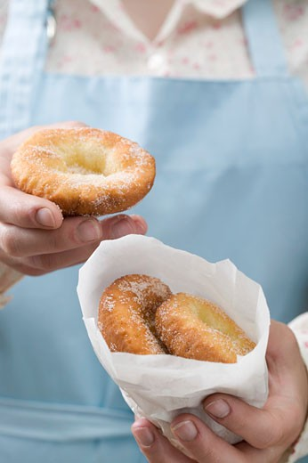 Stock Photo: 1532R-34145 Woman holding Auszogene (Bavarian doughnuts)