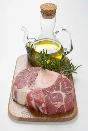 Stock Photo: 1532R-34209 Slice of beef from the leg on chopping board, rosemary, olive oil