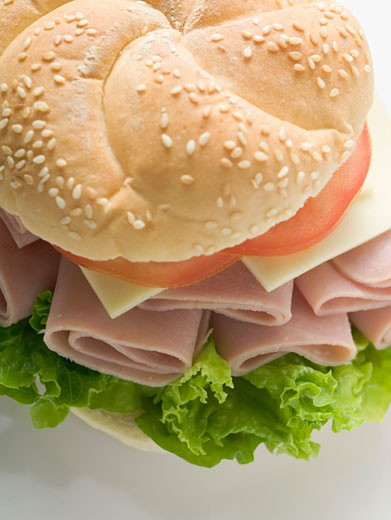 Stock Photo: 1532R-34302 Sesame roll filled with ham, cheese, lettuce and tomato
