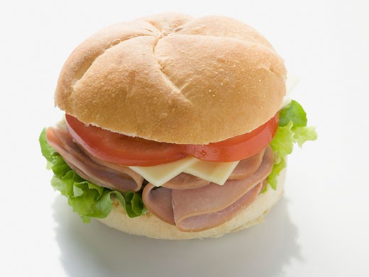 Stock Photo: 1532R-34303 Bread roll filled with ham, cheese, lettuce and tomato