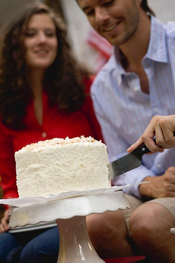 Stock Photo: 1532R-34366 Man cutting coconut cake (4th of July, USA)
