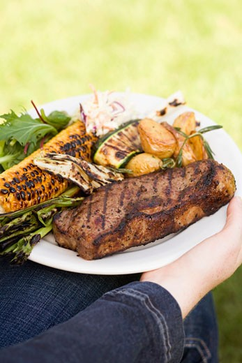 Stock Photo: 1532R-34551 Woman holding plate of steak, grilled vegetables & corn on the cob