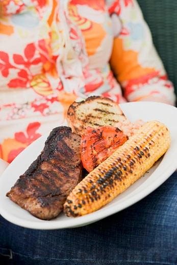 Stock Photo: 1532R-34561 Woman holding a plate of grilled steak and accompaniments