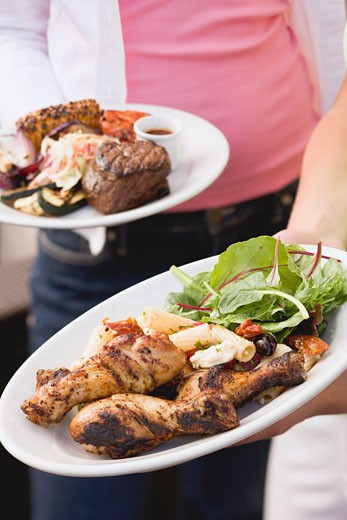 Two people holding plates of grilled food (different) : Stock Photo