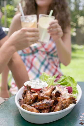 Grilled chicken wings with salad, young people in background : Stock Photo