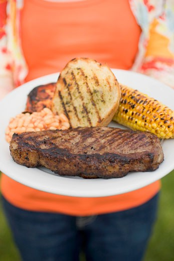 Woman holding plate of steak, bread, corn on the cob, baked beans : Stock Photo