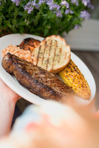 Hands holding plate of steak, bread, corn on the cob, baked beans : Stock Photo