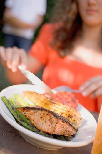 Stock Photo: 1532R-34745 Woman eating grilled salmon with corn on the cob & vegetables
