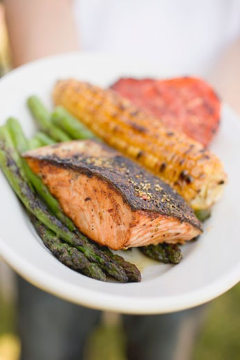Stock Photo: 1532R-34746 Person holding plate of grilled salmon, corn on the cob, vegetables