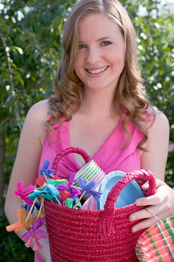 Stock Photo: 1532R-34752 Woman holding basket of decorations for a garden party