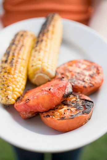 Stock Photo: 1532R-34828 Person holding plate of grilled corn on the cob & tomatoes