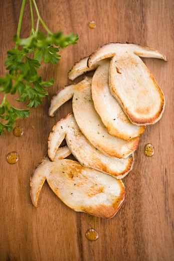 Fried cep slices on wooden background, parsley : Stock Photo