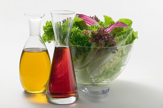 Oil and vinegar in carafes in front of salad bowl : Stock Photo