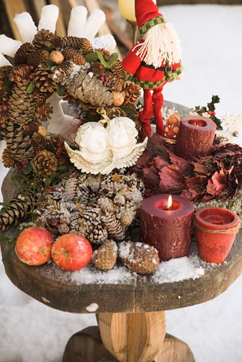 Christmas decorations on wooden table in snowy garden : Stock Photo
