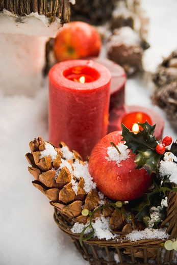 Christmas decorations: apples, cones and candles in snow : Stock Photo