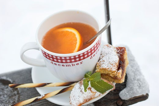 Cup of orange punch with sweet pastries in saucer : Stock Photo