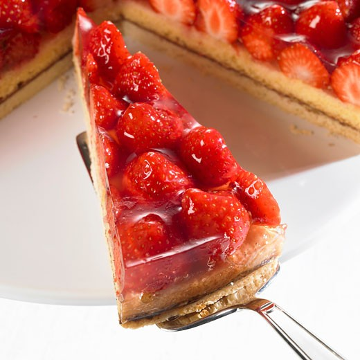 Piece of strawberry flan on server in front of remainder of flan : Stock Photo
