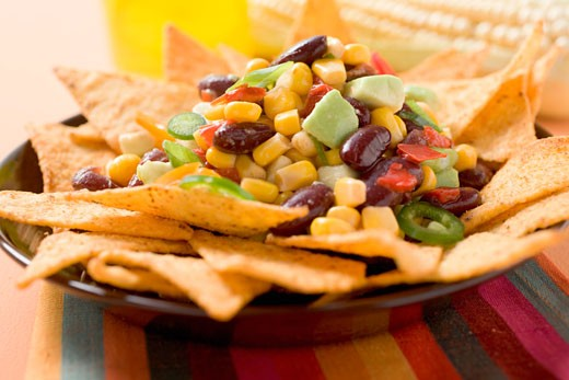 Stock Photo: 1532R-35312 Nachos with beans, sweetcorn, avocado and chilli rings