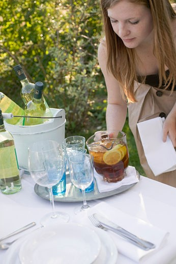 Stock Photo: 1532R-35347 Woman putting a jug of iced tea on table laid in garden