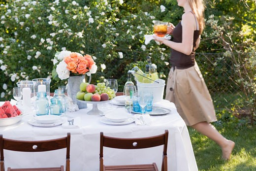 Woman bringing iced tea to table laid in garden : Stock Photo