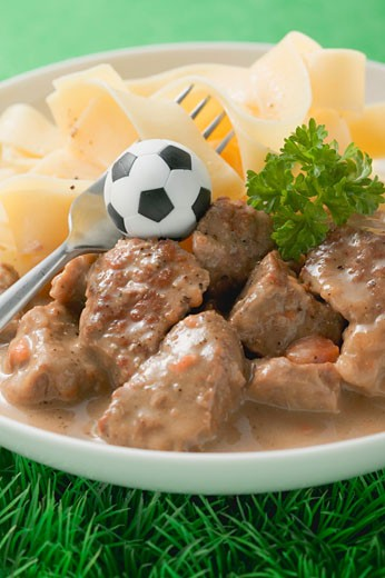 Zürcher Geschnetzeltes (veal dish) with pasta, football & fork : Stock Photo