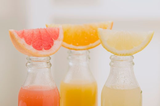 Three fruit juices in bottles with wedges of fresh fruit : Stock Photo