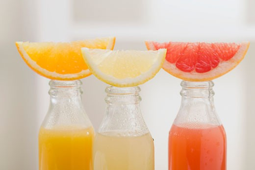 Stock Photo: 1532R-36049 Three fruit juices in bottles with wedges of fresh fruit