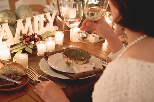 Woman drinking white wine at Christmas meal : Stock Photo