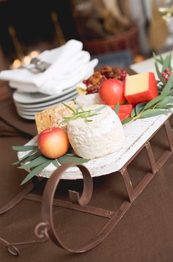 Small sleigh filled with cheese and apples for Christmas : Stock Photo
